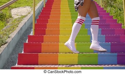 Sexy young woman an a flight of rainbow stairs