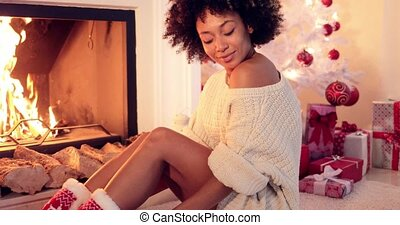 Sexy young woman celebrating Christmas at home sitting on...