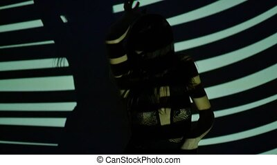 Sexy young woman dancing in the light of the projector. Slow motion. Close-up