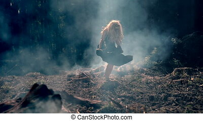 Sexy young woman dancing on the burning-out land. Unusual ...
