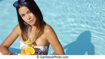 Sexy young woman drinking a tropical cocktail