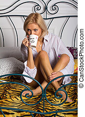 young woman drinking coffee on the bed