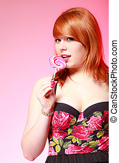 Sexy young woman holding candy. Redhair girl eating sweet...