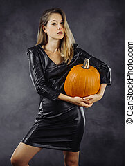 Sexy young woman holding pumpkin for Halloween
