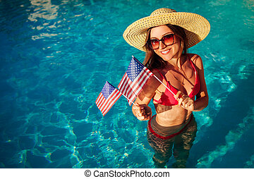 Sexy young woman holding USA flag in swimming pool. Celebrating Independence day of America