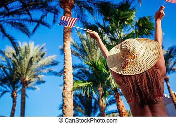 Sexy young woman holding USA flag in under palm trees. Celebrating Independence day of America