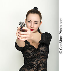 sexy young woman in a black lace bodysuit with braided hair is holding a gun. on the feet thick black stockings