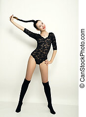 sexy young woman in a black lace bodysuit with braided hair. on the feet thick black stockings. holding his hair