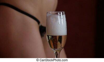 sexy young woman in a mini bikini pours champagne in glasses...