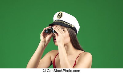 Sexy young woman in a sailor cap looking away with...