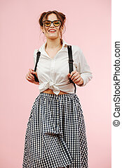 Sexy young woman in a schoolgirl outfit provocatively looking down at a camera. Over pink background. She wears glasses, two buns on her head, checkered skirt and white dress shirt.