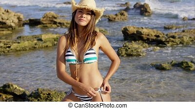 Sexy young woman in a straw hat and bikini