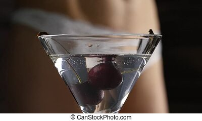 sexy young woman in a white panties prepares a cocktail with...