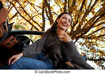 Sexy young woman in jeans smiling in a cabriolet