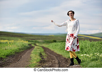 Sexy young woman in skirt hitchhiking near a countryside road