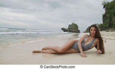 Sexy young woman in the fashion swimsuit lies on the beach on white sand