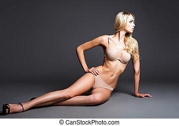 Sexy young woman in underwear sitting on floor. Studio shot