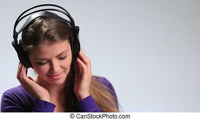 Sexy young woman listening to music playfully