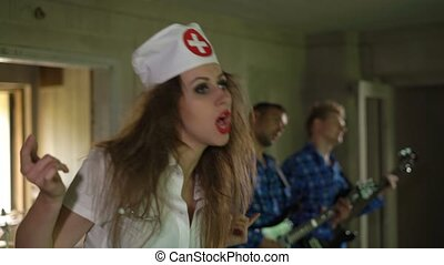 Sexy young woman nurse sings, screams, shouts with crazy patients in psychiatric hospital. Mad guitarist perform with female doctor. Nurse is devil or demon, style as resident evil or silent hill.