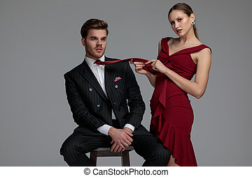 sexy young woman playing with her man's tie