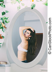 Sexy young woman posing in front of the mirror