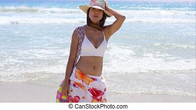 Sexy young woman posing on a tropical beach in a colorful...