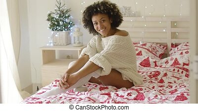 Sexy young woman relaxing on her bed at Christmas in stylish...