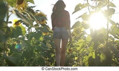 Sexy young woman running through sunflower field