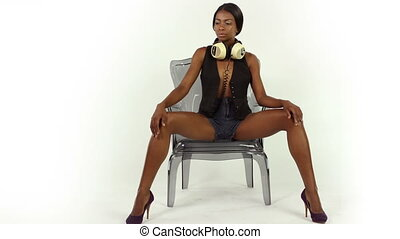 sexy young woman sits in stylish chair listening to music on...