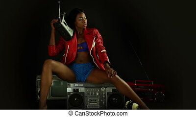 sexy young woman sits ontop of a retro ghettoblaster listening to music on another classic hifi