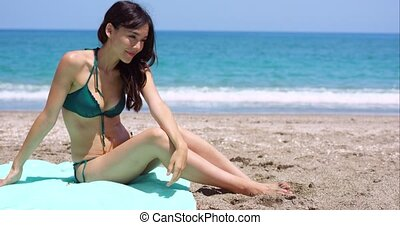 Sexy young woman sitting on a beach
