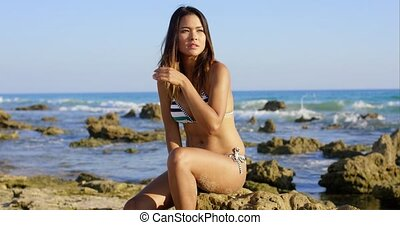 Sexy young woman sitting on rocks at the seaside