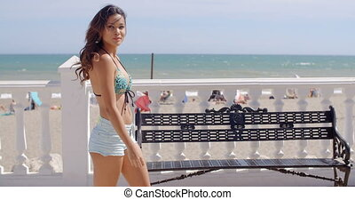 Sexy young woman strolling along a promenade overlooking a...
