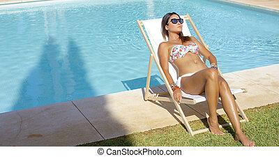 Sexy young woman sunbathing near a pool