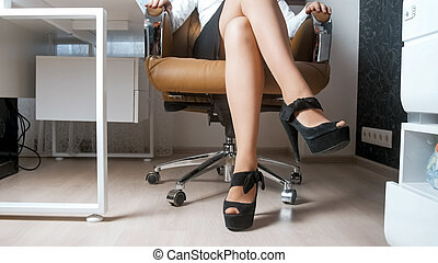 Sexy young woman wearing high heels shoes and short skirt sitting in office chair