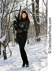 woman with a rifle in winter forest
