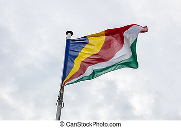 Seychelles flag on a pole waving, cloudy sky background