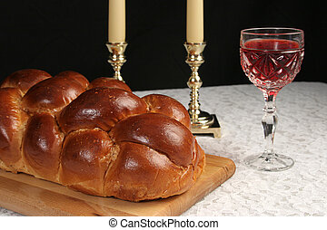 A table set for Shabbat with challah bread, candlesticks and wine. Black background.