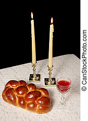 A table set for Shabbat with lighted candles, challah bread and wine. Vertical view with black background.