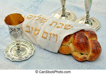 Shabbat eve table with covered challah bread, Sabbath candles and Kiddush wine cup.