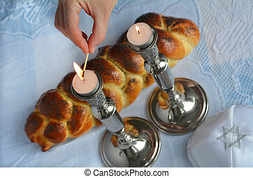 Shabbat eve table.Woman hand lit Shabbath candles with...