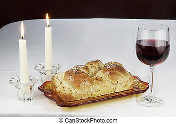 All the elements needed for Shabbat. Challah, glass of wine, t wo lit candles in candlesticks.