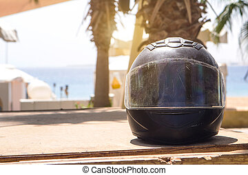 shabby black motorcycle helmet rider in scratches on the background of the red sea and palm trees under the sun for place text