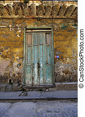 Shabby house entrance in Havana, Cuba. - Green rustic door...