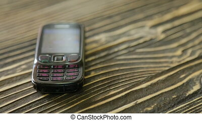 Shabby mobile phone on the texture table - Old mobile phone...