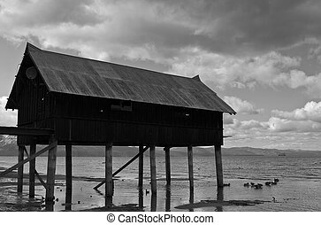 Shack on jetty - Profile of shack on dock with cloudscape in...