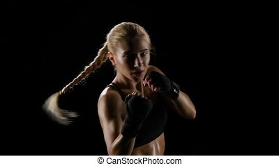 Shadow-boxing blonde girl. Slow motion in the studio