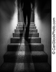 Long exposure photograph of a a tall shadow figure walking up stairs. The image would work well with paranormal themes.