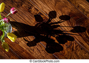 Shadow from a bouquet of tulips on the table