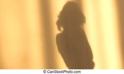 Shadow of a girl on the wall in the sunlight.